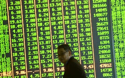 A man stands in front of the electronic board at a stock exchange hall on May 6, 2019 in Hangzhou, Zhejiang Province of China. - Credit: VCG