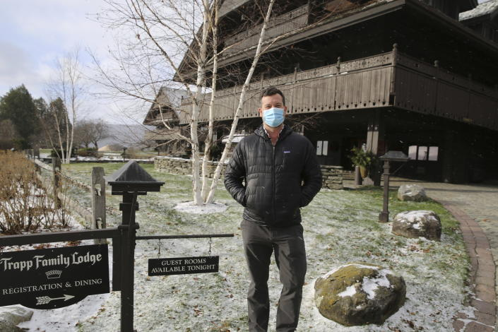 Bob Schwartz, the director of marketing of the Trapp Family Lodge poses outside the lodge on Tuesday, Dec. 15, 2020 in Stowe, Vt. Quarantine rules imposed in an attempt to stop the spread of novel coronavirus are affecting business during the normally busy holiday season. He says the rules are frustrating but be understands the need for them. He's looking forward to a time when the pandemic is over. (AP Photo/Wilson Ring)
