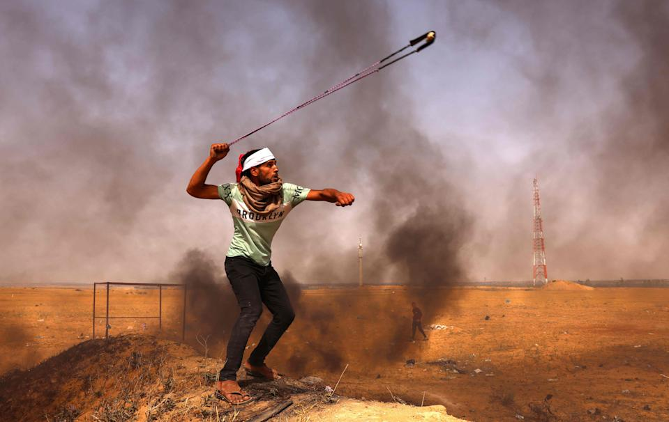 A Palestinian throws rocks earlier todayAFP via Getty Images