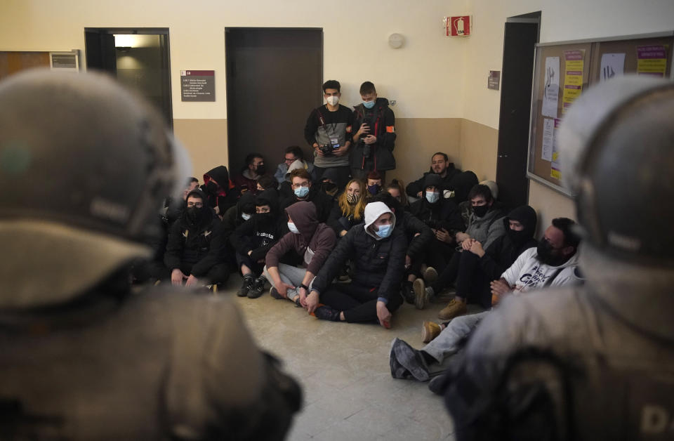 Rap singer Pablo Hasél, background, is surrounded by his supporters as police officers try to arrest him at the University of Lleida, Spain, Tuesday, Feb. 16, 2021. A rapper in Spain and dozens of his supporters have locked themselves inside a university building in the artist's latest attempt to avoid a prison sentence for insulting the monarchy and praising terrorism. (AP Photo/Joan Mateu)