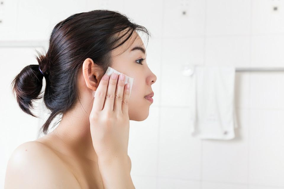 young asian woman removing makeup with wipe
