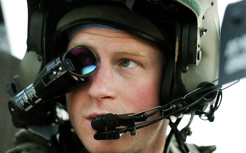 Prince Harry wears his monocle gun sight as he sits in the front seat of his cockpit in Afghanistan - AP