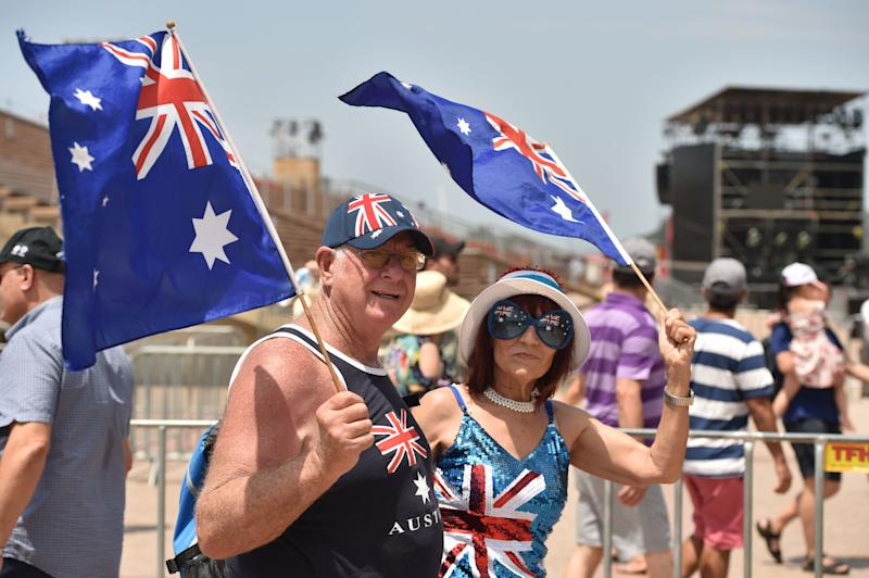 People wave the country's flag to celebrate Australia Day in Sydney.