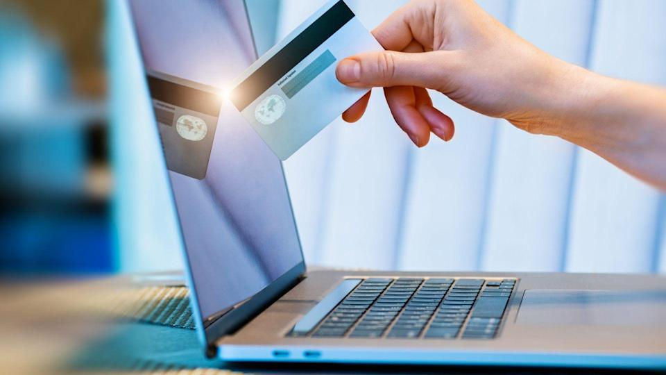 female hand with credit card and online payment using laptop.