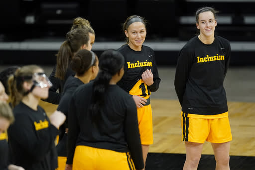 Iowa guard Caitlin Clark, right, laughs with teammates before an NCAA college basketball game against Ohio State, Wednesday, Jan. 13, 2021, in Iowa City, Iowa. Iowa Freshman Caitlin Clark is fourth in the nation in scoring at 25.6 points per game. (AP Photo/Charlie Neibergall)