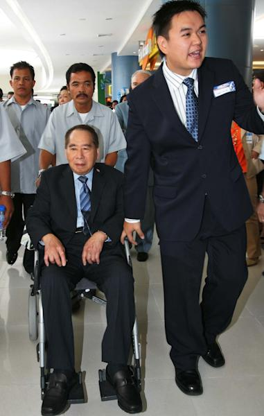 FILE - In this May 20, 2006 file photo, Henry Sy Sr., left, patriach of the Sy family and chairman of the SM Prime Holdings Inc. sits on the wheel chair as he is escorted by his grandson Hans Sy Jr. right, during the opening of the SM Mall of Asia in suburban Pasay City, south of Manila, Philippines. Macau gambling company Melco Crown Entertainment is teaming up with the Philippines' richest man to develop a $1 billion Manila casino resort in a sign of the industry's plans for rapid expansion in Asia. Melco said late Thursday, July 5, 2012 it will develop the project with three companies controlled by Philippine tycoon Henry Sy. Melco is jointly controlled by Lawrence Ho, who is the son of Macau casino king Stanley Ho, and by James Packer, the son of late Australian media magnate Kerry Packer. (AP Photo/Pat Roque, File)