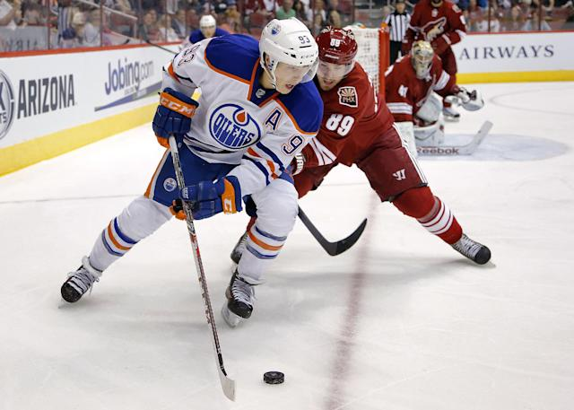 Edmonton Oilers' Ales Hemsky (93) and Phoenix Coyotes' Mikkel Boedker, of Denmark, battle for the puck during the first period of an NHL hockey game, Saturday, Oct. 26, 2013, in Glendale, Ariz. (AP Photo/Matt York)