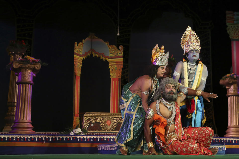 FILE- In this Nov. 2, 2015, file photo, Indian actors dressed as Rama, right, Dasharatha, center, and Laxman, the characters of Hindu epic Ramayana perform at a theatre in Bangalore, India. Seeking comfort in the certainty of the past, Indians are tuning into re-runs of popular Hindu religious dramas, drawing on shared experiences of old times when most questions had answers. Staying home under a lockdown as they wait for the worst of the coronavirus pandemic to pass, millions of Indians are turning to their Gods. Not in their prayer rooms, but on their televisions. (AP Photo/Aijaz Rahi, File)