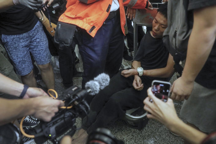 Cameramen and photographers film a detained man, who protesters claimed was a police officer from mainland China, on a luggage trolley during a demonstration at the Airport in Hong Kong, Tuesday, Aug. 13, 2019. (Photo: Vincent Yu/AP)
