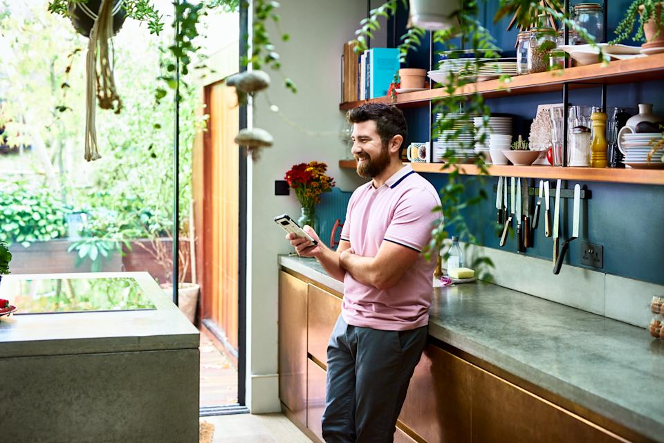 Cheerful man standing in kitchen using phone, relaxed, home interior, communication