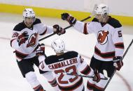 New Jersey Devils center Travis Zajac, left, is congratulated by teammates Mike Cammalleri (23) and Adam Larsson (5) after his goal against the Boston Bruins during the first period of an NHL hockey game in Boston, Monday, Nov. 10, 2014. (AP Photo/Charles Krupa)
