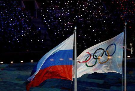 FILE PHOTO: The Russian national flag flutters next to the Olympics flag during the closing ceremony for the 2014 Sochi Winter Olympics, February 23, 2014.  REUTERS/Issei Kato/File Photo