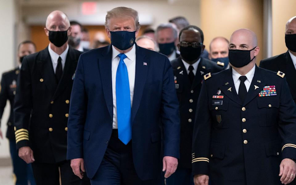 US President Donald J. Trump (C) wears a face mask as he arrives to visit with wounded military members and front line coronavirus healthcare workers at Walter Reed National Military Medical Center in Bethesda, Maryland, USA - CHRIS KLEPONIS/POOL/EPA-EFE/Shutterstock