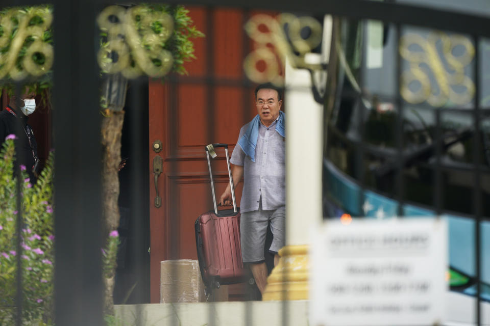 Kim Yu Song, counselor at the North Korean Embassy to Malaysia, carries his luggage into a bus at the embassy in Kuala Lumpur, Sunday, March 21, 2021. Malaysia on Friday ordered all North Korean diplomats to leave the country within 48 hours, an escalation of a diplomatic spat over Malaysia's move to extradite a North Korean suspect to the United States on money laundering charges. (AP Photo/Vincent Thian)