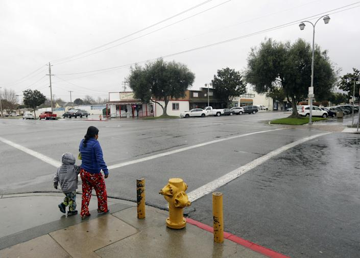 A woman and child cross an intersection on Wednesday, Feb. 26, 2014, in King City, Calif. The acting police chief and two officers in King City were removed from duty after being arrested on suspicion of selling or giving away the impounded cars of poor residents, authorities said. (AP Photo/Marcio Jose Sanchez)