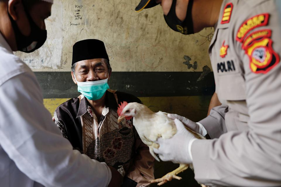 Lili Dinata, 72-year-old local of Sindanglaya village, is being rewarded with a live chicken by Galih Apria, the district police chief, after receiving his first dose of a COVID-19 vaccine, during a door-to-door vaccination in Cianjur regency, West Java province, Indonesia, June 15, 2021. REUTERS/Willy Kurniawan