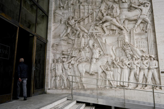 """A man enters a building where a marble bas-relief titled """"The Story of Rome through its Constructions"""", made in 1940 by sculptor Publio Morbiducci, shows from top to bottom the history of Rome from its foundation to the fascist period with its dictator Benito Mussolini on a horse, in the EUR neighborhood of Rome, Monday, May 6, 2019. Mussolini transformed Rome's urban landscape with grand construction projects like EUR, a new city district that was originally designed as celebration of fascism for a world fair in 1942. The fair was canceled due to WWII and construction was halted but resumed after the war. (AP Photo/Andrew Medichini)"""