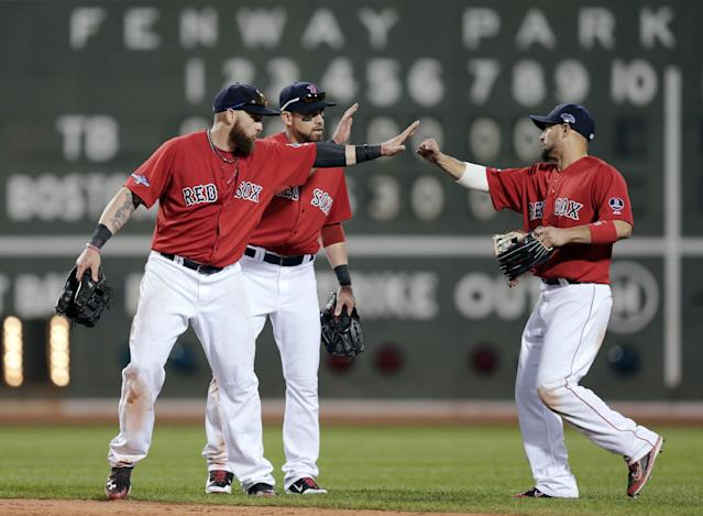 Boston Red Sox outfielders Jonny Gomes, left, Jacoby Ellsbury, center, and Shane Victorino celebrate their 12-2 win over the Tampa Bay Rays in Game 1 of baseball's American League division series, Friday, Oct. 4, 2013, in Boston. (AP Photo/Charles Krupa)