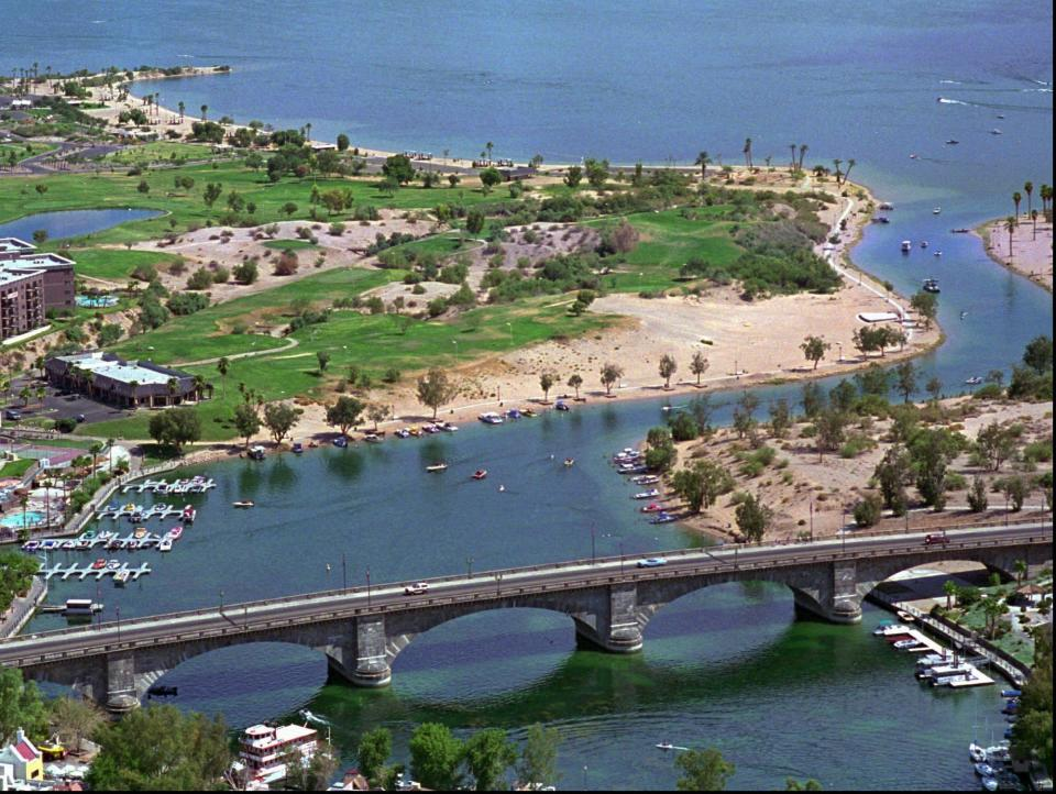 FILE - In this July 22, 1994 file photo the London Bridge stands in the foreground with State Beach, behind, and Rotary Beach, around the corner, in the background in this aerial at Lake Havasu, Ariz. Lake Havasu City is playing up its roots with a month of celebratory events marking the 50th anniversary of the dedication of the London Bridge after its piece-by-piece rebuild in the resort town along the Colorado River. Scheduled October events include a parade, powerboat racing, theater and musical performances, sports competitions and a garden brunch and tea. (AP Photo/Jeff Robbins,File)