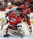 Carolina Hurricanes goalie Justin Peters (35) eyes the puck moving toward the net with teammate Eric Staal (12) and Philadelphia Flyers' Claude Giroux (28) nearby during the first period of an NHL hockey game on Saturday, April 20, 2013, in Raleigh, N.C. (AP Photo/Karl B DeBlaker)