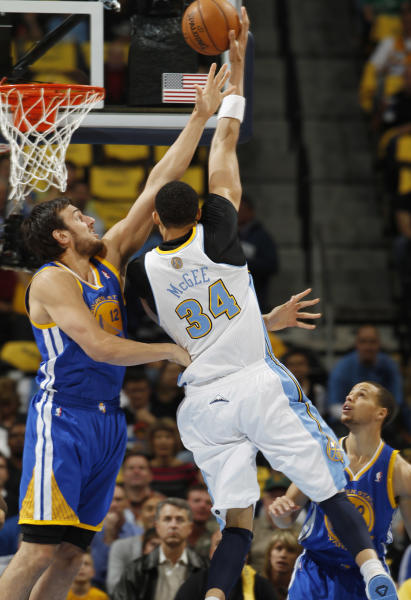 Golden State Warriors center Andrew Bogut, left, of Australia, reaches up to block a shot by Denver Nuggets forward JaVale McGee during the first quarter of Game 5 of their first-round NBA basketball playoff series, Tuesday, April 30, 2013, in Denver. (AP Photo/David Zalubowski)