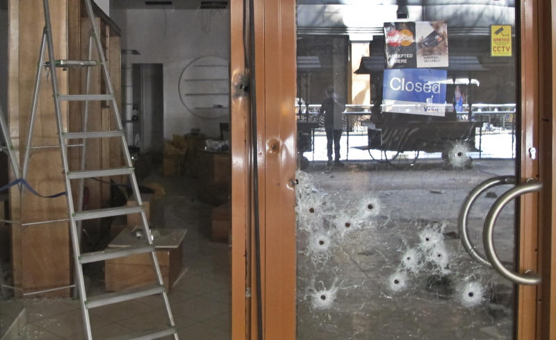 FILE - In this Tuesday, Oct. 1, 2013 file photo, bullet-holes pepper the glass door of a shop in the Westgate Mall in Nairobi, Kenya. The Sept. 21 terrorist attack on Nairobi's Westgate Mall produced a raft of questions that haven't always had clear, complete answers and the answers to some questions have changed over time - The Associated Press attempts to define what is known and not known about the deadly mall attack. (AP Photo/Rukmini Callimachi, File)