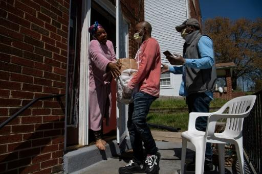 Anthony Lorenzo Green (R) and Bernard Stevenson (C) deliver groceries to a woman in Washington during the coronavirus pandemic