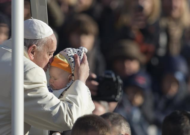 Pope Francis holds a baby as he arrives for his weekly general audience in St. Peter's Square at the Vatican, Wednesday, Dec. 18, 2013. (AP Photo/Alessandra Tarantino)