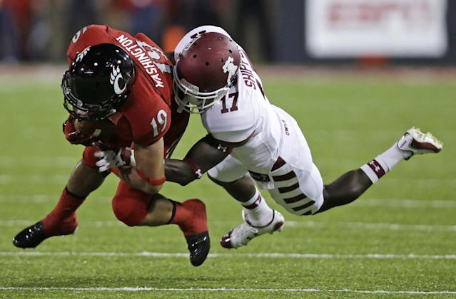 Cincinnati wide receiver Shaq Washington (19) is tackled by Temple defensive back Brandon Shippen (17) after a short gain in the first half of an NCAA college football game, Friday, Oct. 11, 2013, in Cincinnati. (AP Photo/Al Behrman)