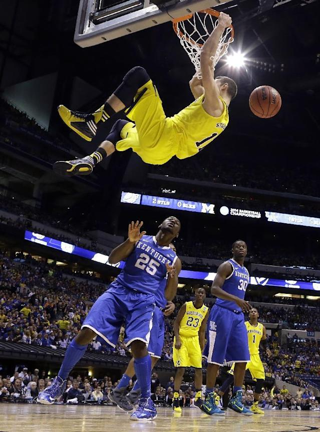 Michigan's Nik Stauskas, center, dunks over Kentucky's Dominique Hawkins during the second half of an NCAA Midwest Regional final college basketball tournament game, Sunday, March 30, 2014, in Indianapolis. (AP Photo/Michael Conroy)