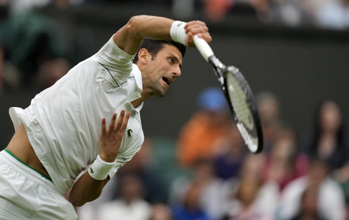 Serbia's Novak Djokovic serves to Britain's Jack Draper during their first round men's singles match on day one of the Wimbledon Tennis Championships in London, Monday June 28, 2021. (AP Photo/Kirsty Wigglesworth)