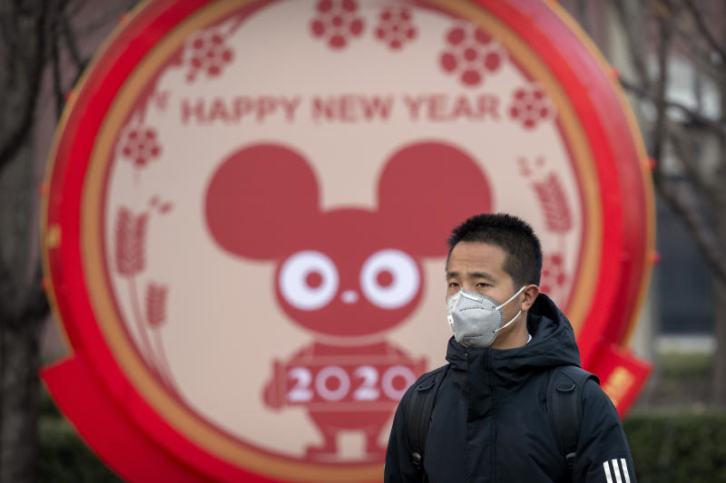 FILE - In this Jan. 22, 2020 photo, a man wears a face mask as he walks past a display for the upcoming Lunar New Year, the Year of the Rat, in Beijing, Wednesday, Jan. 22, 2020. A virus that has killed more than two dozen people and sickened hundreds more has all but shut down China's biggest holiday of the year, the Lunar New Year. Instead of family reunions or sightseeing trips, many of the country's 1.4-billion people are hunkering down as the country scrambles to prevent the illness from spreading further. (AP Photo/Mark Schiefelbein, File)