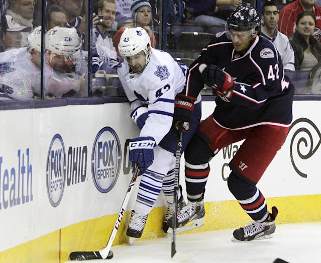 Toronto Maple Leafs' Nazem Kadri, left, and Columbus Blue Jackets' Artem Anisimov, of Russia, chase a loose puck during the first period of an NHL hockey game on Friday, Oct. 25, 2013, in Columbus, Ohio. (AP Photo/Jay LaPrete)