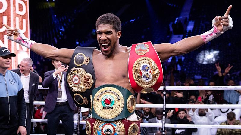 Pictured here, Anthony Joshua celebrates with his heavyweight titles.