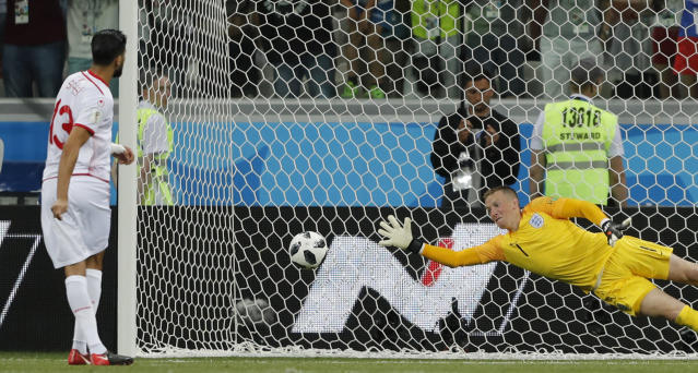 Tunisia's Ferjani Sassi, left, scores a penalty against England goalkeeper Jordan Pickford during the group G match between Tunisia and England at the 2018 soccer World Cup in the Volgograd Arena in Volgograd, Russia, Monday, June 18, 2018. (AP Photo/Frank Augstein)