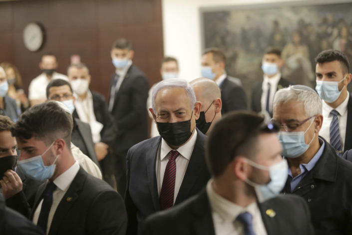 Israeli Prime Minister Benjamin Netanyahu, center, leaves the Israeli Knesset (Parliament) after a vote on the dissolution of the Knesset, in Jerusalem, Wednesday, Dec. 2 2020. The Israeli parliament passed a preliminary proposal to dissolve itself on Wednesday, setting up a possible fourth national election in under two years while the country is in the grip of the coronavirus pandemic. (Alex Kolomoisky/Pool via AP)