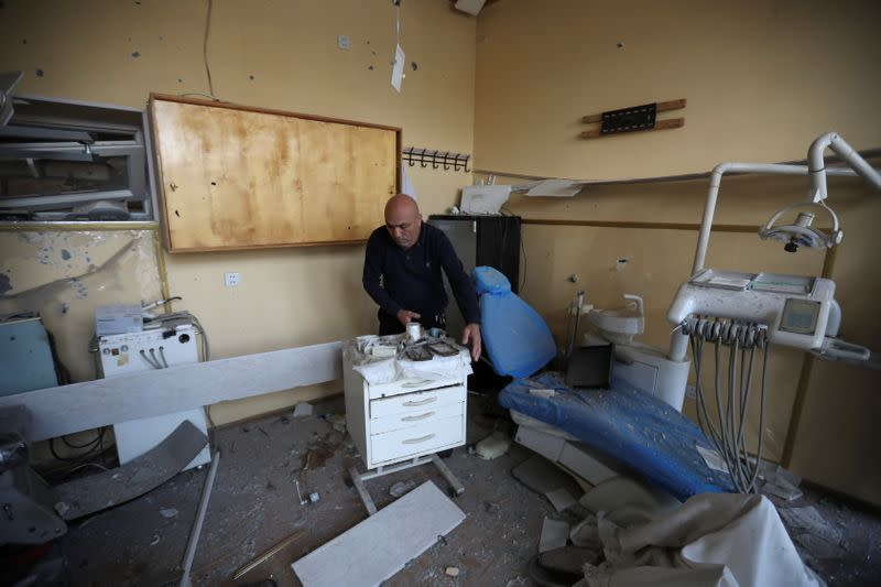A man removes debris inside a medical room following shelling in Barda