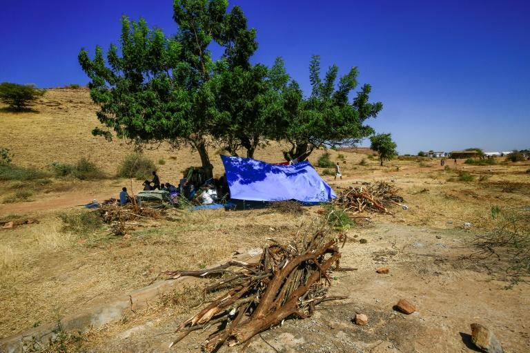 People sit in the shade of a tree next to mattresses, beds, and belongings at the Um Raquba camp in Sudan's eastern Gedaref province, where thousands of refugees have fled to from Ethiopia's Tigray conflict