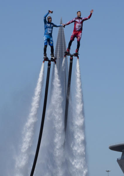 Members of the Russian hydroflight team perform during the Day of Russia celebration in St.Petersburg, Russia, Friday, June 12, 2020, with business tower Lakhta Centre, the headquarters of Russian gas monopoly Gazprom in the background. (AP Photo/Dmitri Lovetsky)