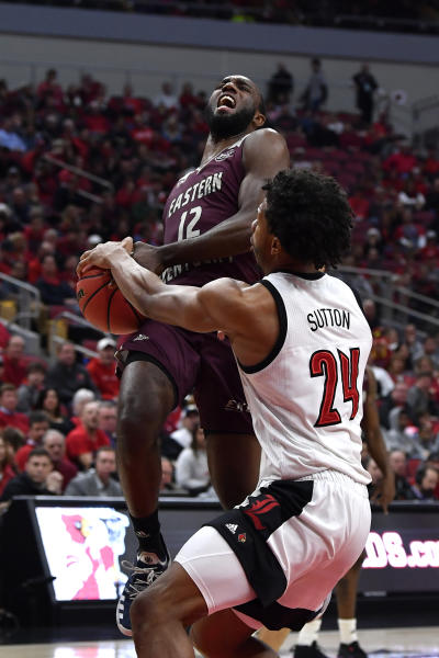 Louisville forward Dwayne Sutton (24) strips the ball away from Eastern Kentucky guard Ty Taylor II (12) as he goes in for a layup during the first half of an NCAA college basketball game in Louisville, Ky., Saturday, Dec. 14, 2019. (AP Photo/Timothy D. Easley)