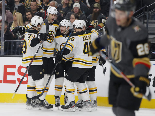 Players celebrate after Boston Bruins left wing Jake DeBrusk, third from left, scored against the Vegas Golden Knights during the first period of an NHL hockey game Wednesday, Feb. 20, 2019, in Las Vegas. (AP Photo/John Locher)
