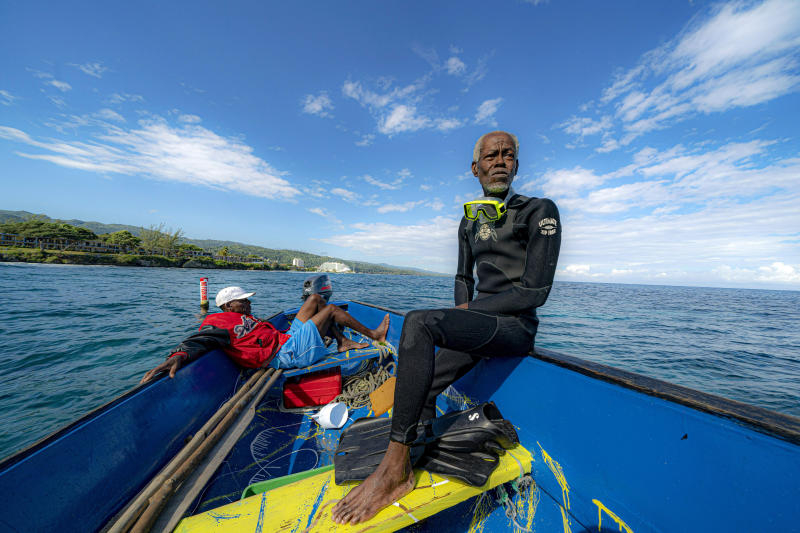 Everton Simpson, right, sits on a boat in-between dives on the White River Fish Sanctuary with Mark Lobban, left, Monday, Feb. 11, 2019, in Ocho Rios, Jamaica. More than a dozen grassroots-run fish sanctuaries and coral nurseries have sprung up on the island in the past decade.  (AP Photo/David J. Phillip)