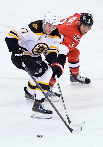 Ottawa Senators' Marc Methot, right, knocks the puck off the stick of Boston Bruins' Milan Lucic during the first period of an NHL hockey game in Ottawa, Ontario on Friday, Nov. 15, 2013. (AP Photo/The Canadian Press, Sean Kilpatrick)