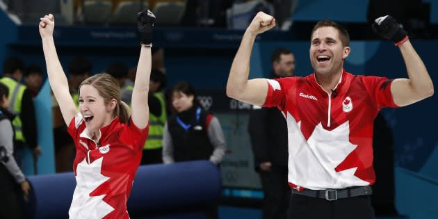 John Morris celebrates with teammate Kaitlyn Lawes of Canada after winning the gold medal against Switzerland in mixed doubles curling.
