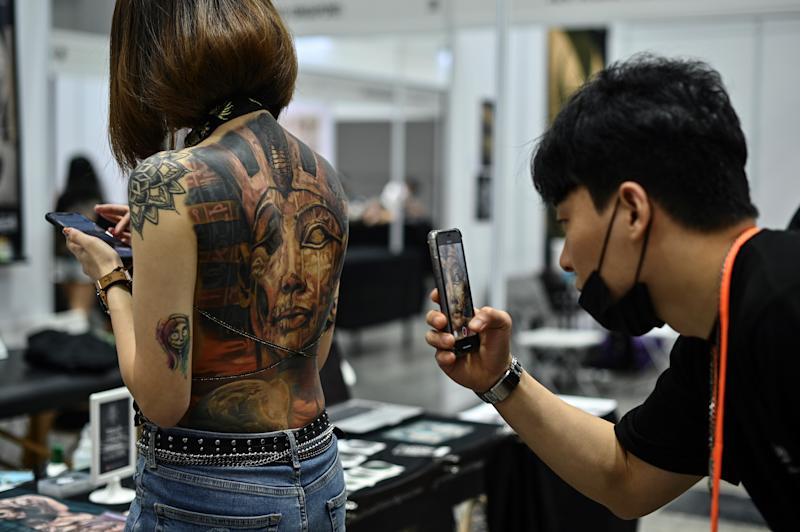 A man takes pictures of a woman with tattoos during the International Malaysia Tattoo Expo in Kuala Lumpur on November 29, 2019. - The international tattoo expo is held for the first ime in Kuala Lumpur celebrating that art of tattoo and gathering over a hundred tattoo artists from 40 countries. (Photo by Mohd RASFAN / AFP) (Photo by MOHD RASFAN/AFP via Getty Images)