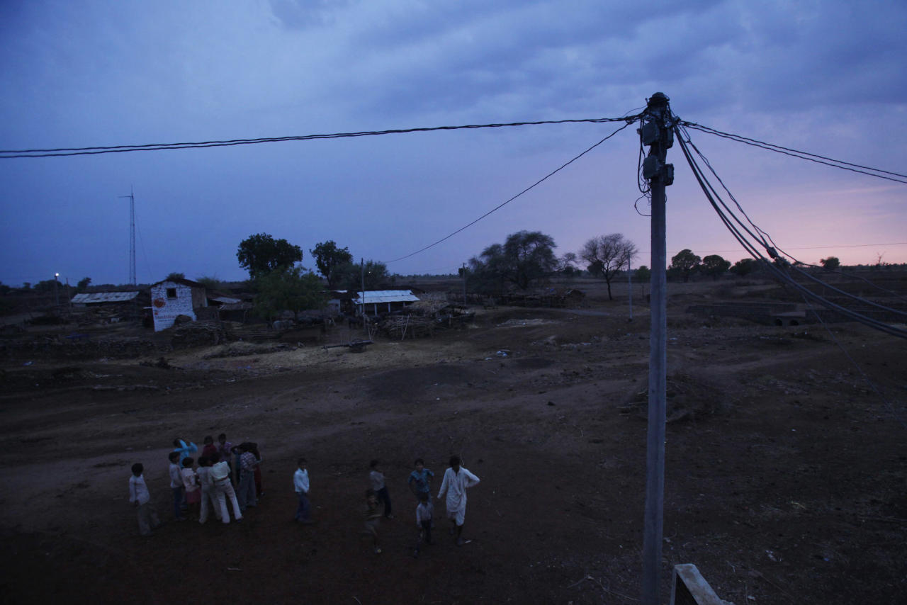 Villagers stand under an electric pole powered by solar energy at Meerwada village of Guna district in the central Indian state of Madhya Pradesh June 18, 2012. REUTERS/Adnan Abidi