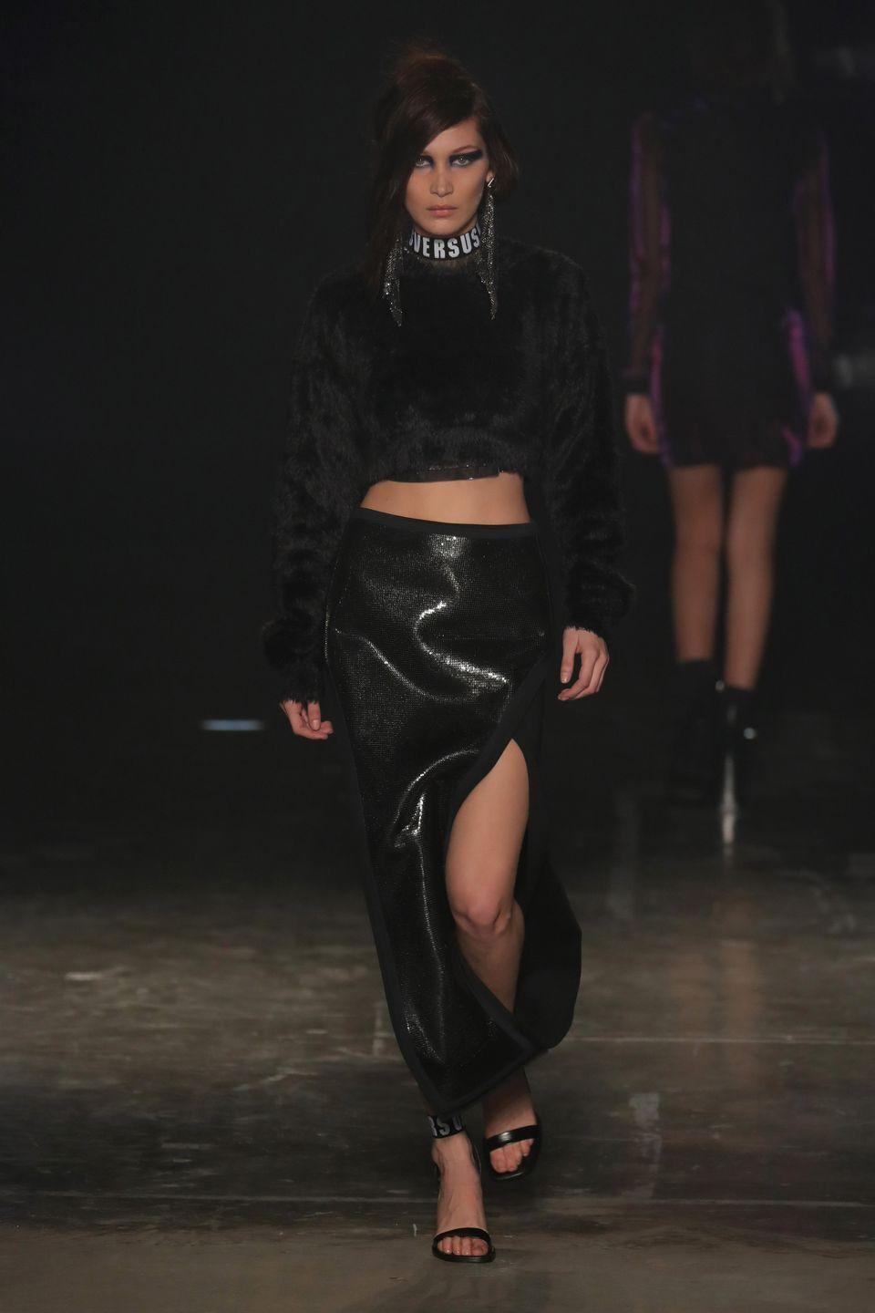 <p>Bella walked the Versus Versace runway wearing a black jumper and a high-thigh slit skirt during London Fashion Week</p>