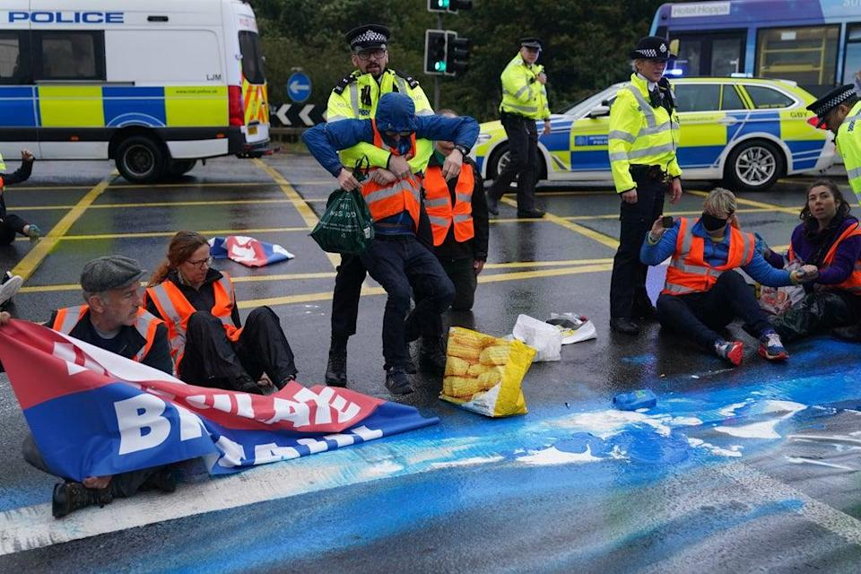 Police officers detain protesters from Insulate Britain occupying a roundabout leading from the M25 motorway to Heathrow Airport in London (Steve Parsons/PA) (PA Wire)