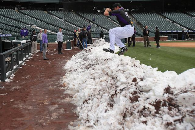 DENVER, CO - APRIL 16: Pitcher Rex Brothers of the Colorado Rockies jumps over a snow bank to get to the dugout as workers remove snow from the field as the New York Mets and the Colorado Rockies prepare for a double header at Coors Field on April 16, 2013 in Denver, Colorado. All uniformed team members are wearing jersey number 42 in honor of Jackie Robinson Day. (Photo by Doug Pensinger/Getty Images)