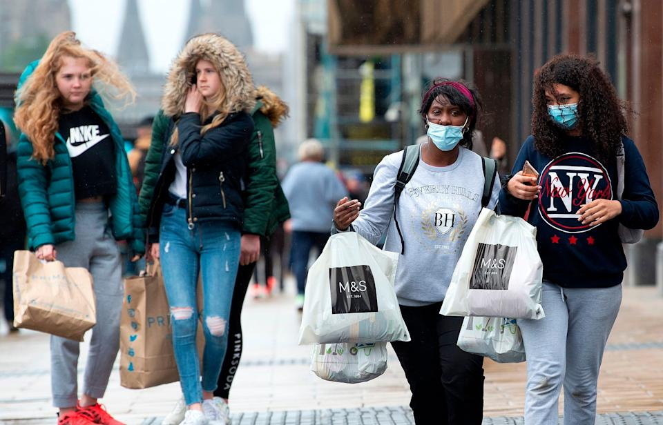 Shoppers in Scotland. Some are wearing masks, others aren't. (Photo: LESLEY MARTIN via Getty Images)